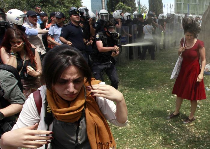 Ένας Τούρκος αστυνομικός ρίχνει δακρυγόνο καθώς οι άνθρωποι διαμαρτύρονται για την καταστροφή των δέντρων σε ένα πάρκο από ένα πεζό έργο, στην Πλατεία Ταξίμ στο κέντρο της Κωνσταντινούπολης, στις 28 Μαΐου 2013. (Reuters / Osman Orsal)