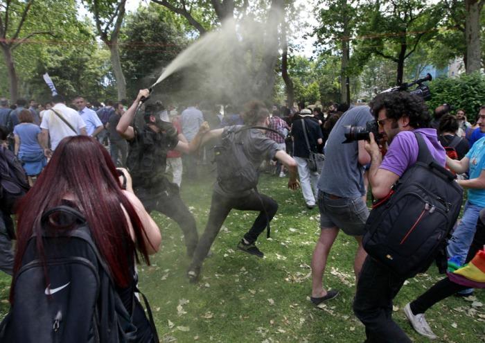 Ένας Τούρκος αστυνομικός ρίχνει δακρυγόνο καθώς οι άνθρωποι διαμαρτύρονται για την καταστροφή των δέντρων σε ένα πάρκο που θα ξεκινούσε στην Πλατεία Ταξίμ στην Κωνσταντινούπολη, στις 28 Μαΐου 2013. (Reuters / Osman Orsal)