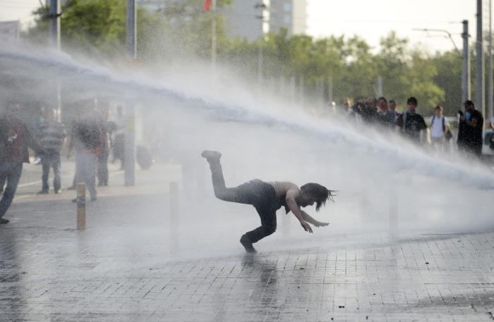 Διαδηλωτές φεύγουν από ένα κανόνι νερού κατά τη διάρκεια συγκρούσεων με την αστυνομία, στις 31 του Μάη 2013 κατά τη διάρκεια μιας διαμαρτυρίας στην Πλατεία Ταξίμ στην Κωνσταντινούπολη. (AFP / Getty Images)