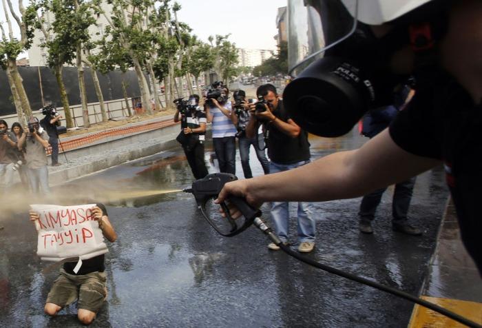 """Ένας Τούρκος αστυνομικός χρησιμοποιεί δακρυγόνο καθώς ο διαδηλωτής κρατά ένα πανό που γράφει: """"Χημικός Ταγίπ"""", αναφερόμενος στον πρωθυπουργό Ταγίπ Ερντογάν, κατά τη διάρκεια διαδήλωσης στην Πλατεία Ταξίμ, την 31η Μαΐου 2013. (Reuters / Murad Sezer)"""