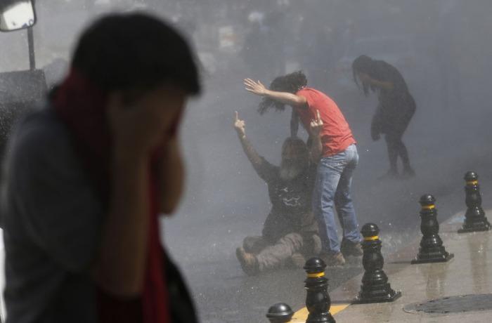 Ένας διαδηλωτής αντιδρά στους αστυνομικούς που χρησιμοποιούν ένα κανόνι νερού και δακρυγόνα για να διαλύσουν το πλήθος στην Πλατεία Ταξίμ, στις 31 Μαΐου 2013. (Reuters / Murad Sezer)