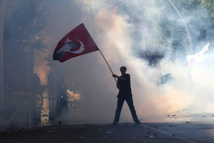 Δακρυγόνο περιβάλλει ένα διαδηλωτή που κυμματίζει μια τουρκική σημαία με ένα πορτρέτο του ιδρυτή της σύγχρονης Τουρκίας Μουσταφά Κεμάλ Ατατούρκ ενώ ο ίδιος παίρνει μέρος σε μια διαδήλωση για την υποστήριξη των διαδηλώσεων στην Κωνσταντινούπολη και κατά του Πρωθυπουργού της Τουρκίας και του κυβερνώντος Κόμματος Δικαιοσύνης και Ανάπτυξης Κόμματος, στην Άγκυρα , την 1η Ιουνίου 2013. (Adem Altan / AFP / Getty Images)
