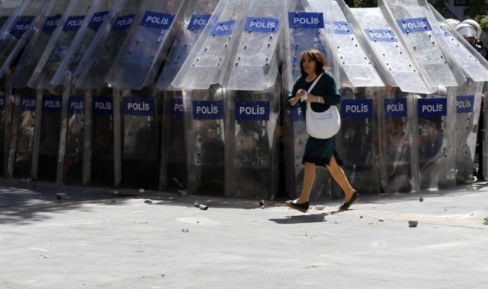 Μια γυναίκα περνάει τρέχοντας μπροστά από τους αστυνομικούς που κρύβονται πίσω από τις ασπίδες τους κατά τη διάρκεια συγκρούσεων με διαδηλωτές που διαμαρτύρονταν εναντίον του Πρωθυπουργού της Τουρκίας Ταγίπ Ερντογάν και το κυβερνών Κόμμα Δικαιοσύνης και Ανάπτυξης στο κέντρο της Άγκυρας, την 1 Ιουνίου 2013. (Reuters / Umit Bektas)