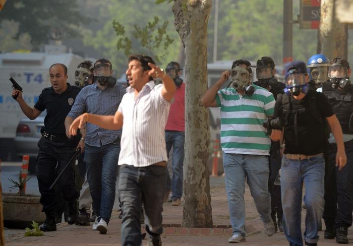 Αστυνομία και άνδρες της ασφάλειας αντιμετωπίζουν διαδηλωτές στην κεντρική Πλατεία Ταξίμ της πόλης, την 1η Ιουνίου 2013. (AP Photo)