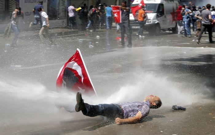 Ένας άνδρας χτυπιέται από έναν πίδακα νερού καθώς η αστυνομία χρησιμοποιεί μια αντλία νερού για να διαλύσει τους διαδηλωτές κατά τη διάρκεια μιας διαμαρτυρίας εναντίον του Πρωθυπουργού της Τουρκίας Ταγίπ Ερντογάν στο κέντρο της Άγκυρας, την 1η Ιουνίου 2013. (Reuters / Umit Bektas)