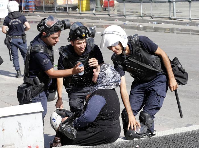 Αστυνομικοί βοηθούν μια γυναίκα που επλήγει από τα δακρυγόνα που ρίχτηκαν κατά τη διάρκεια συγκρούσεων με διαδηλωτές στην Άγκυρα, την 1η Ιουνίου 2013. (Reuters / Umit Bektas)