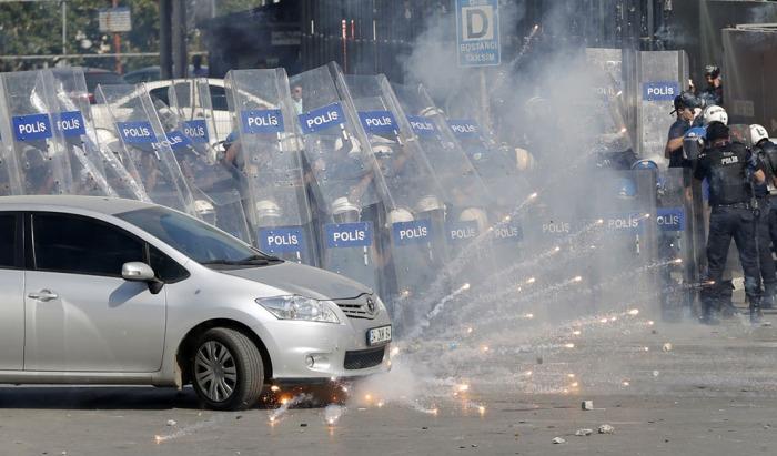 Αστυνομικοί πίσω από ασπίδες πυροβολούν δακρυγόνα καθώς συγκρούονται με αντικυβερνητικούς διαδηλωτές στην Πλατεία Ταξίμ, την 1η Ιουνίου 2013. (Reuters / Murad Sezer)