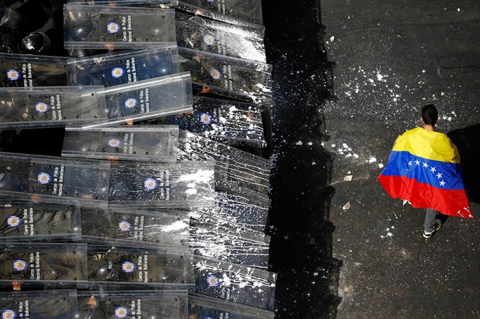 A demonstrator with a Venezuelan flag draped around himself protests against the government of Venezuela's President Maduro, in front of a riot police line in Caracas