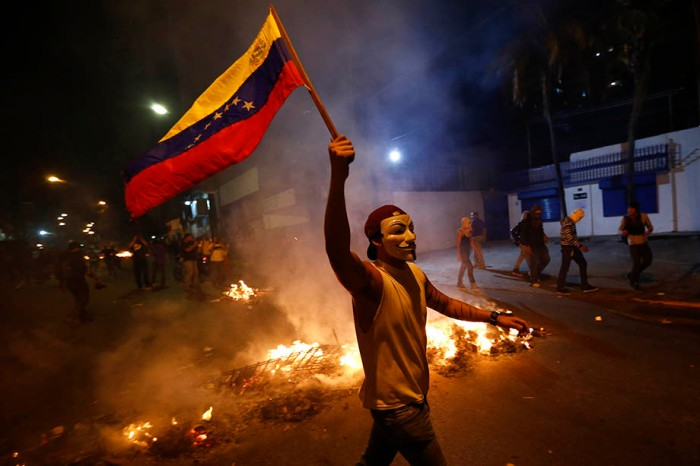 An opposition demonstrators holds a Venezuelan flag in front of a burning barricade in Caracas
