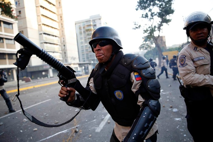 Riot police shoots tear gas as they fight against students during a protest in Caracas
