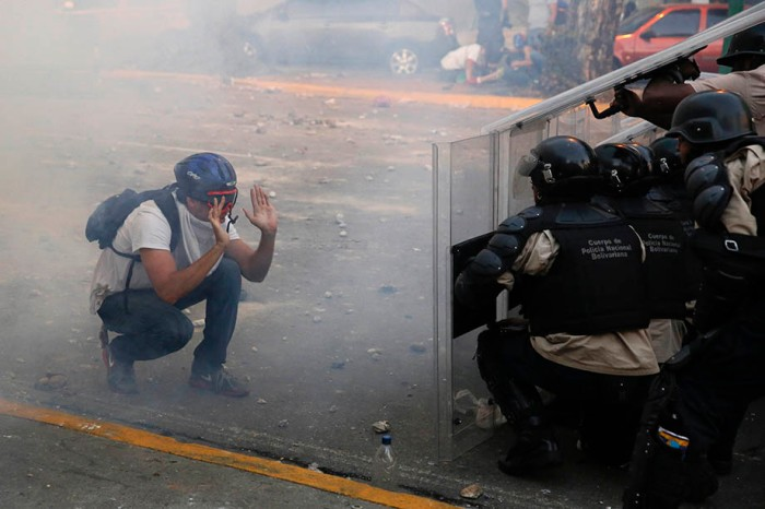 An opposition demonstrator confronts riot police during a protest in Caracas