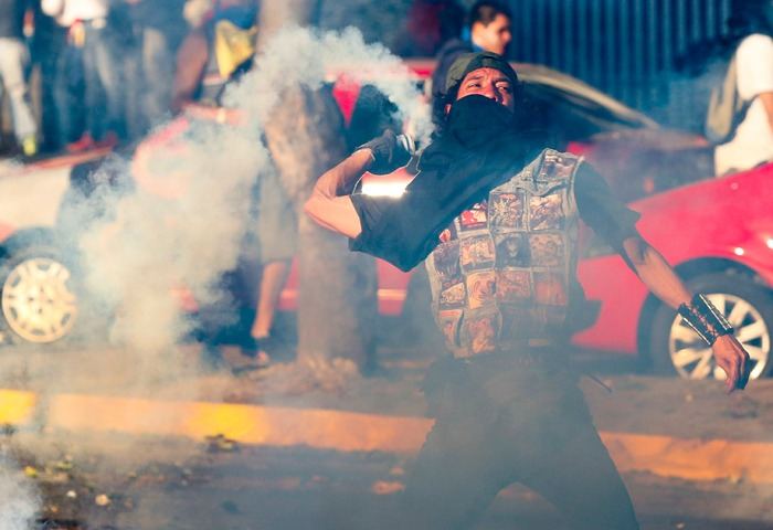 An opposition demonstrator throws a gas canister back to riot po