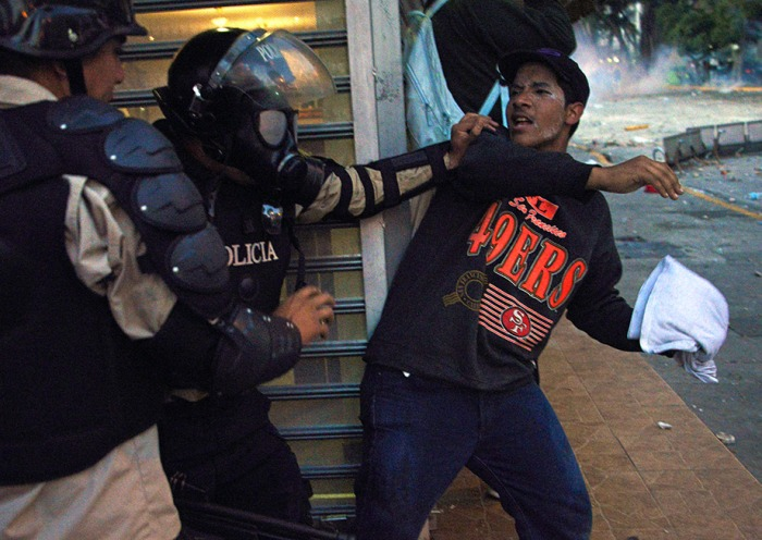 A member of the National Police struggles with an anti-governmen