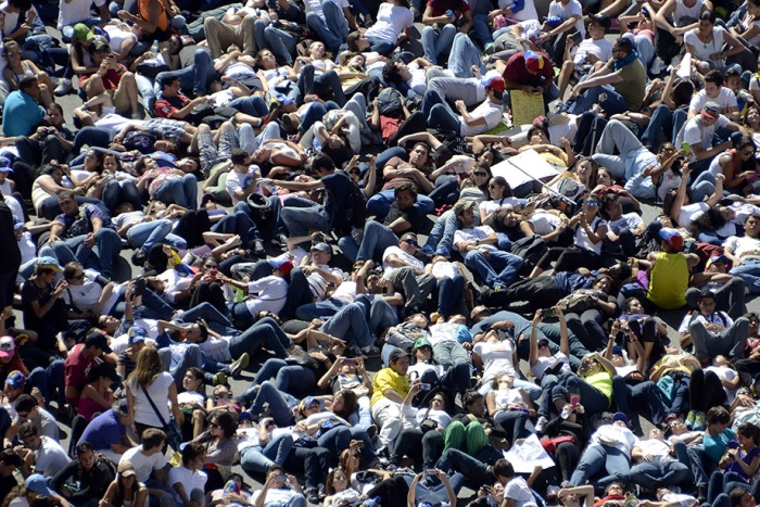Thousands of anti-government students lie on the ground during a