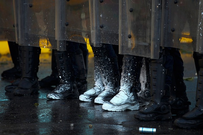 Riot police officers clash with opposition demonstrators during
