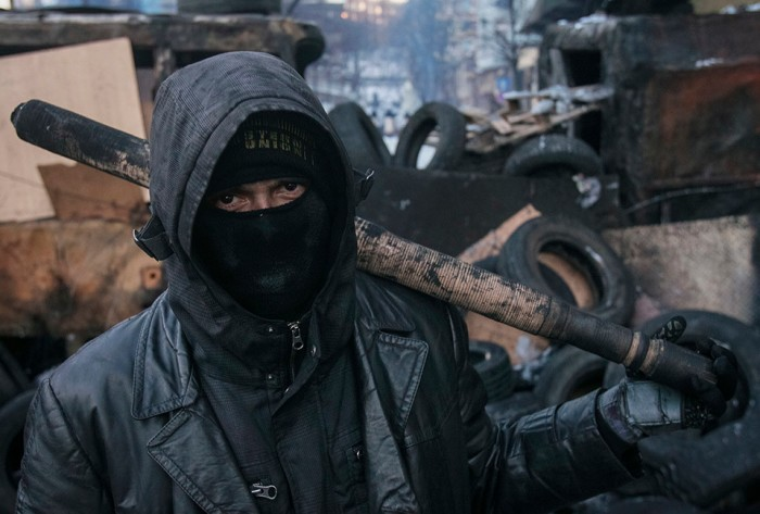 Anti-government protester stands on barricades at the site of clashes with riot police in Kiev