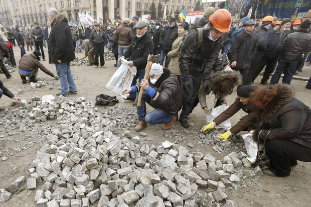 Anti-government protesters gather stones during a rally in central Kiev