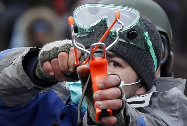 A pro-European integration protester uses a slingshot during clashes with police in Kiev