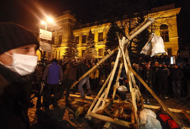 Pro-European integration protesters build a catapult to throw stones during clashes with police in Kiev
