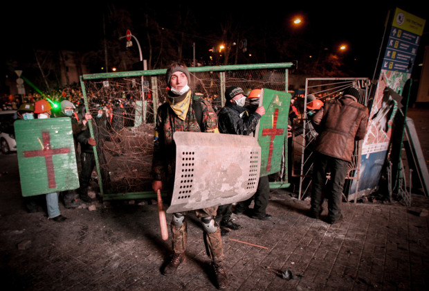Pro-European integration protesters take cover behind shields during clashes with Ukrainian riot police in Kiev