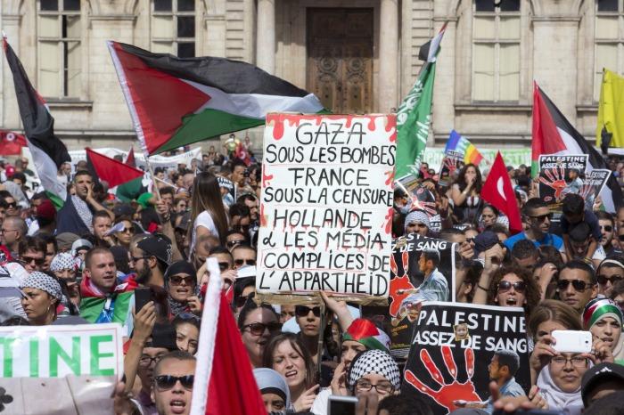 Διαδηλωτές με πλακάτ που αναγράφουν συνθήματα εναντίον της λογοκρισίας των media στη Γαλλία και του Ολάντ σε πορεία στη Λυών
