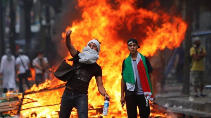 Διαδηλωτής εκσφενδονίζει πέτρες εναντίον της αστυνομίας στα επεισόδια που ακολούθησαν στο Παρίσι
