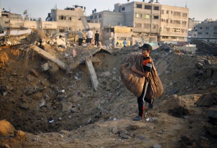 Ένα αγόρι στα συντρίμμια του σπιτιού του στη Γάζα