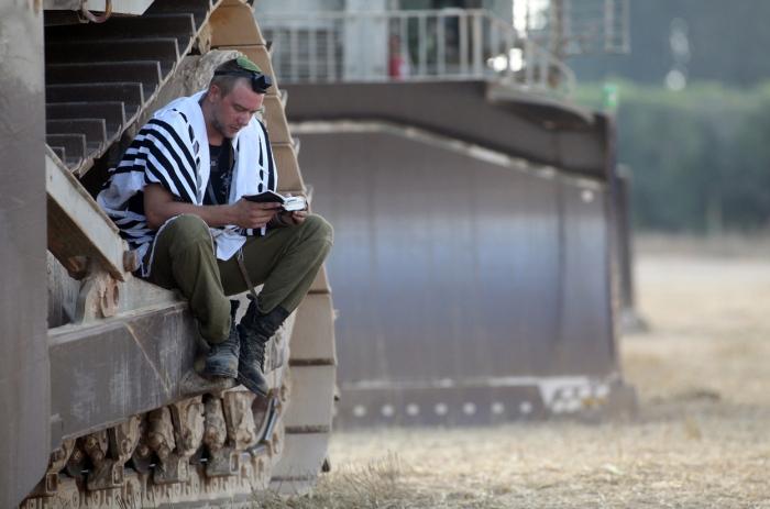 Ισραηλινός στρατιώτης διαβάζει προσευχές στα χαρακώματα των συνόρων Ισραήλ και Γάζας.