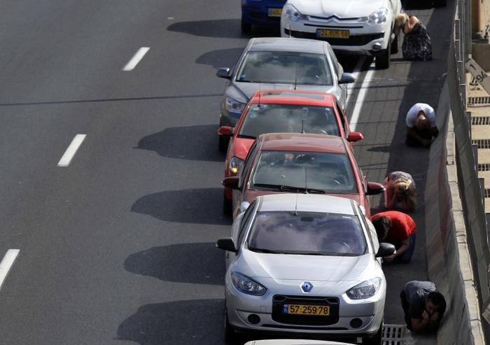 Στο άκουσμα των σειρήνων οι οδηγοί στο Τελ Αβιβ μετακινούν τα οχήματά τους στην άκρη του δρόμου και κουλουριάζονται δίπλα τους.