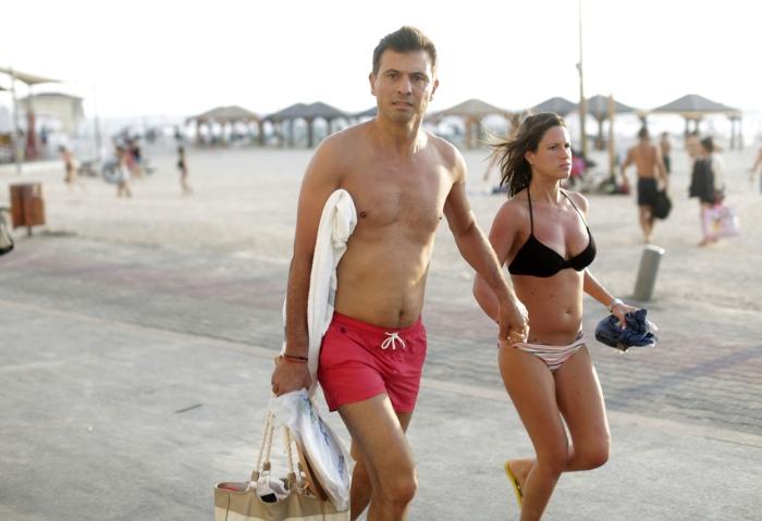 Ένα ζευγάρι απομακρύνεται από την παραλία στο Τελ Αβίβ καθώς ακούγονται οι σειρήνες που προειδοποιούν για επιδρομή.
