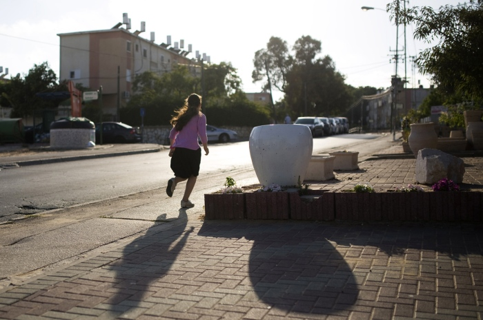 Ένα νεαρό κορίτσι τρέχει προς το σπίτι της καθώς ακούγονται οι προειδοποιητικές σειρήνες στην πόλη Ασκαλώνα